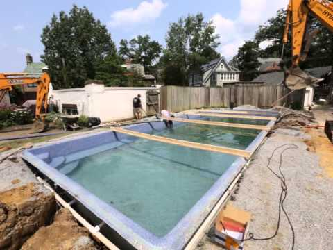 Local pool builders measuring and installing a viking pool for Local swimming pool companies